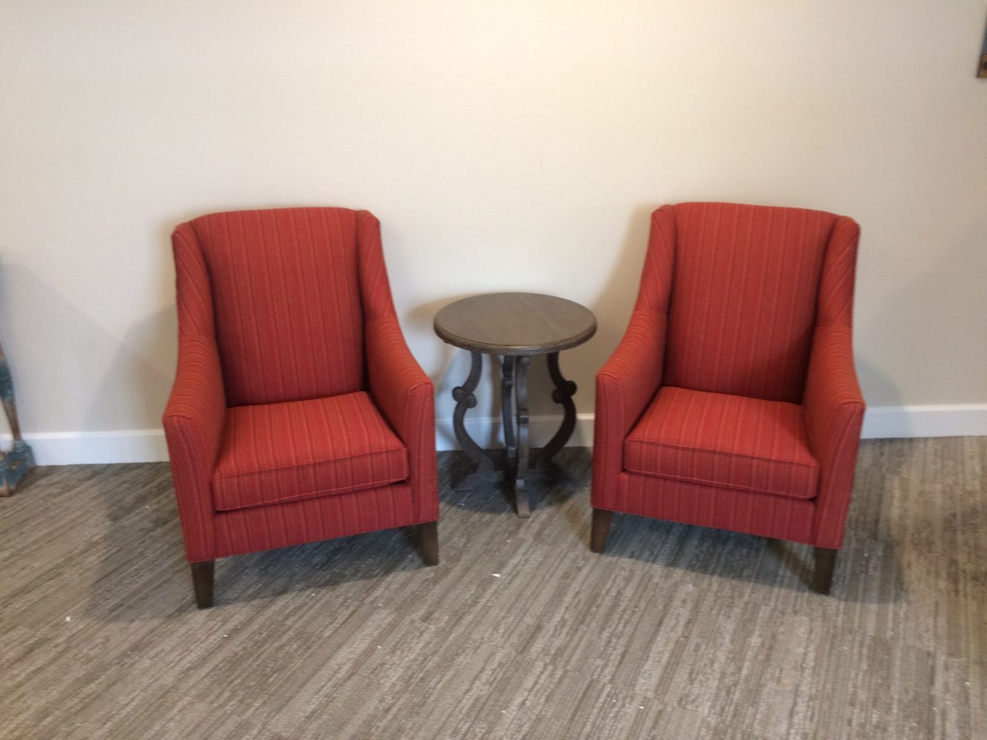 two red chairs with an end table