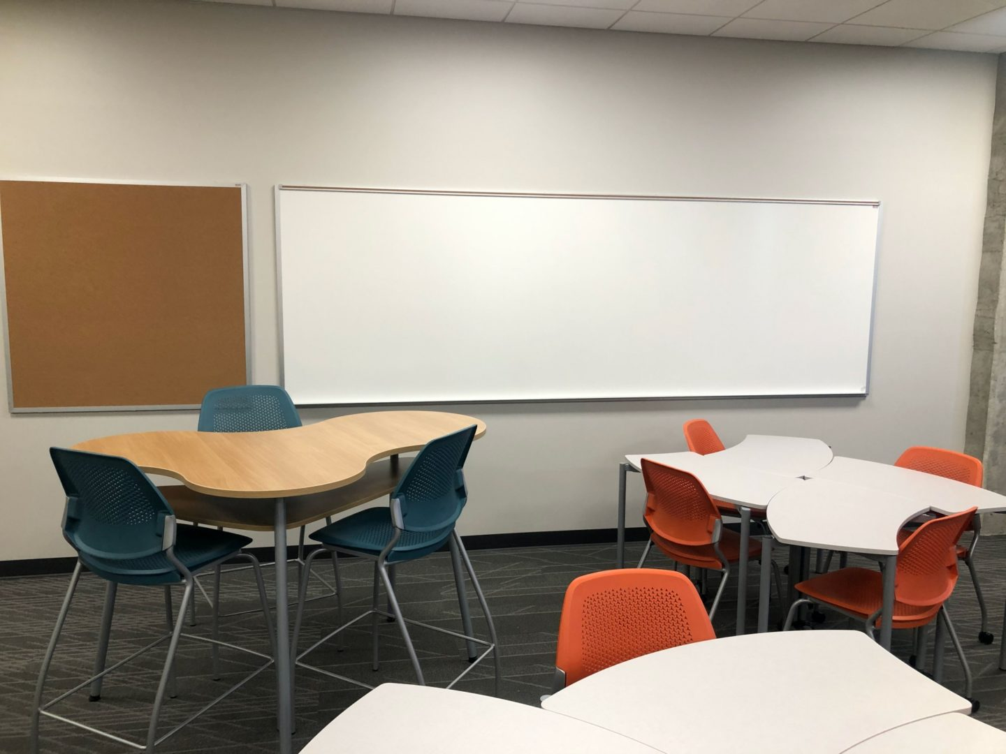 classroom with whiteboard, tables, and chairs