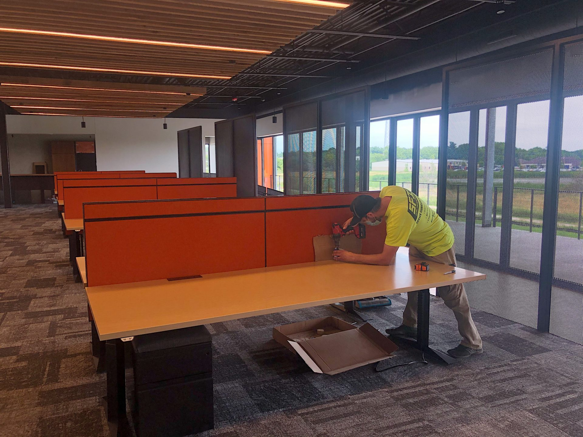 worker installing office cubicle walls